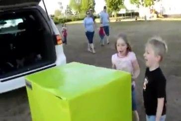 Deux enfants déballent un cadeau contenant leur père militaire