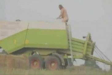 Un fermier passe à travers une moissonneuse-batteuse