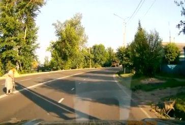 Bon conducteur aide une dame à traverser la route
