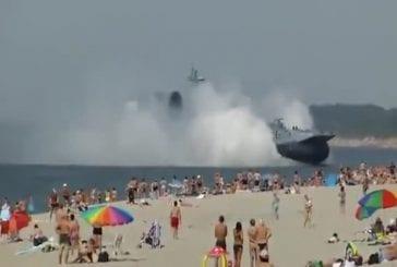 Aéroglisseur militaire traverse une plage bondée