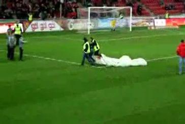 Un supporter arrive en parachute à un match de football