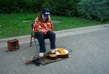 Homme joue de la guitare avec les orteilles