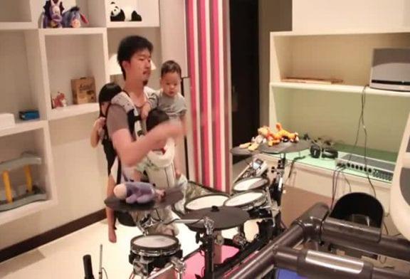 Papa joue Killer One-Armed Drum en portant ses 3 bébés