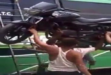 Indien monte avec sa tête une moto sur le toit d'un bus