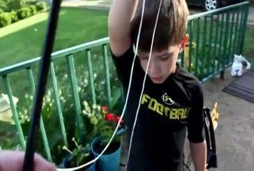 Les gamins sans peur tire sa dent lâche avec un arc et des flèches