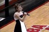 Basketteur aide une jeune fille à chanter l'hymne national